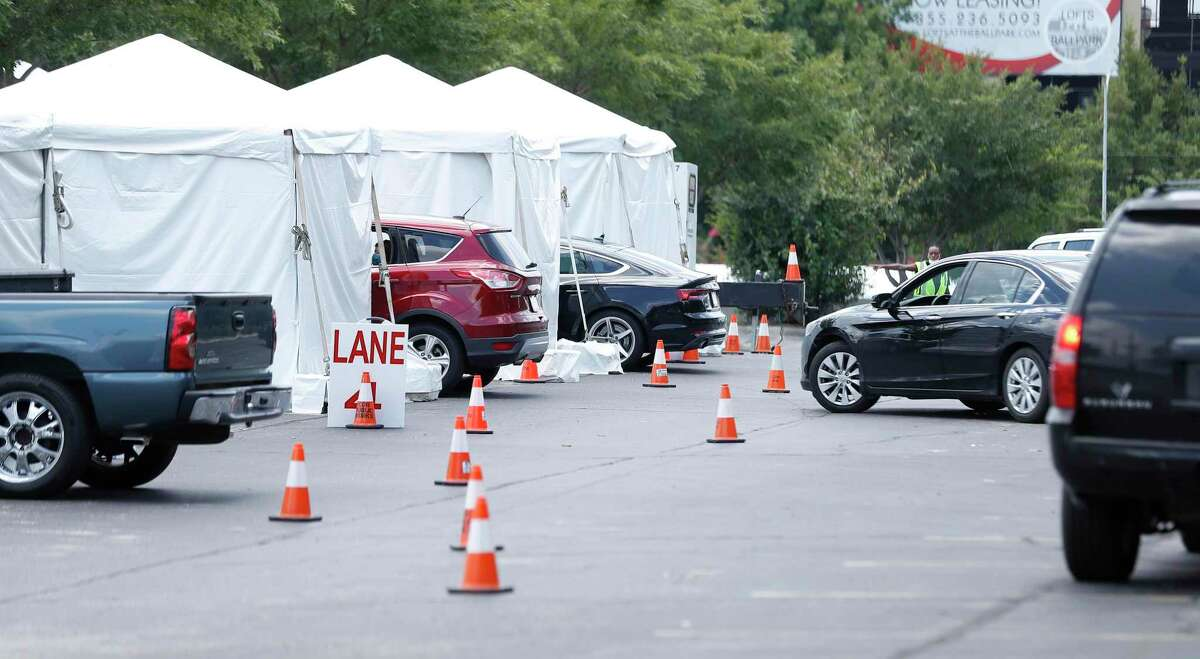 Cars line up next to tents as the Houston Astros opened up a Covid-19 testing site in parking Lot C, Saturday, August 8, 2020, in Houston. Located near Minute Maid Park, the testing site is capable of 2,000 tests a day.