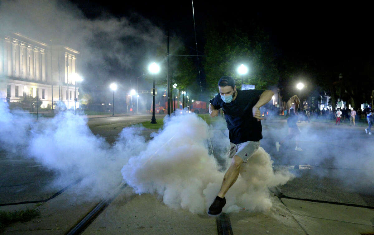 A man jumps over a tear gas canister as he is fired upon with rubber bullets filed by Kenosha County Sheriff's Department officers in downtown Kenosha on Sunday, Aug. 23, 2020. (Sean Krajacic/Kenosha News via AP)