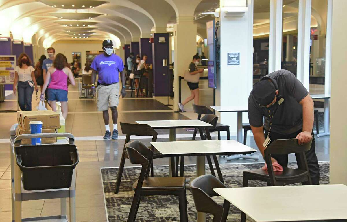 A man is seen sanitizing tables and chairs in the dining hall in the campus center at University at Albany on Monday, Aug. 24, 2020 in Albany, N.Y. Students start their first day of class in the first semester. (Lori Van Buren/Times Union)