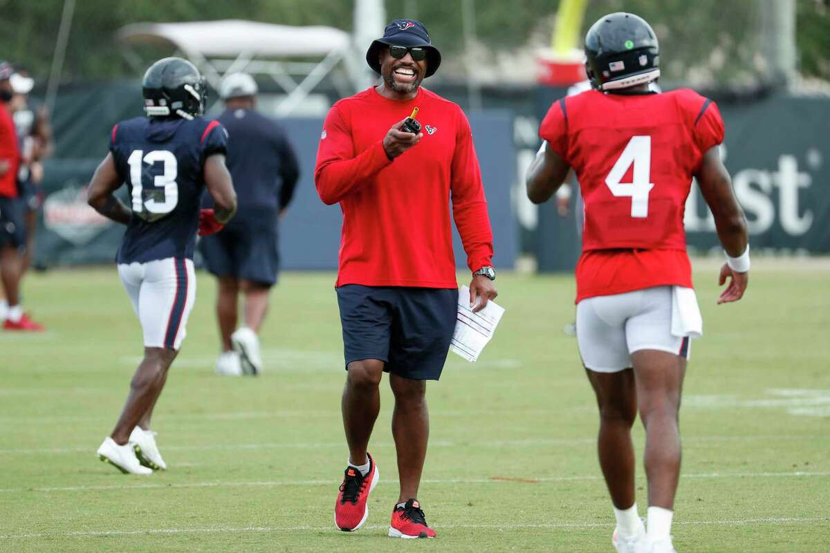 Houston Texans defensive coordinator Anthony Weaver, left, laughs with quarterback Deshaun Watson (4) between drills during an NFL training camp football practice Monday, Aug. 24, 2020, in Houston.