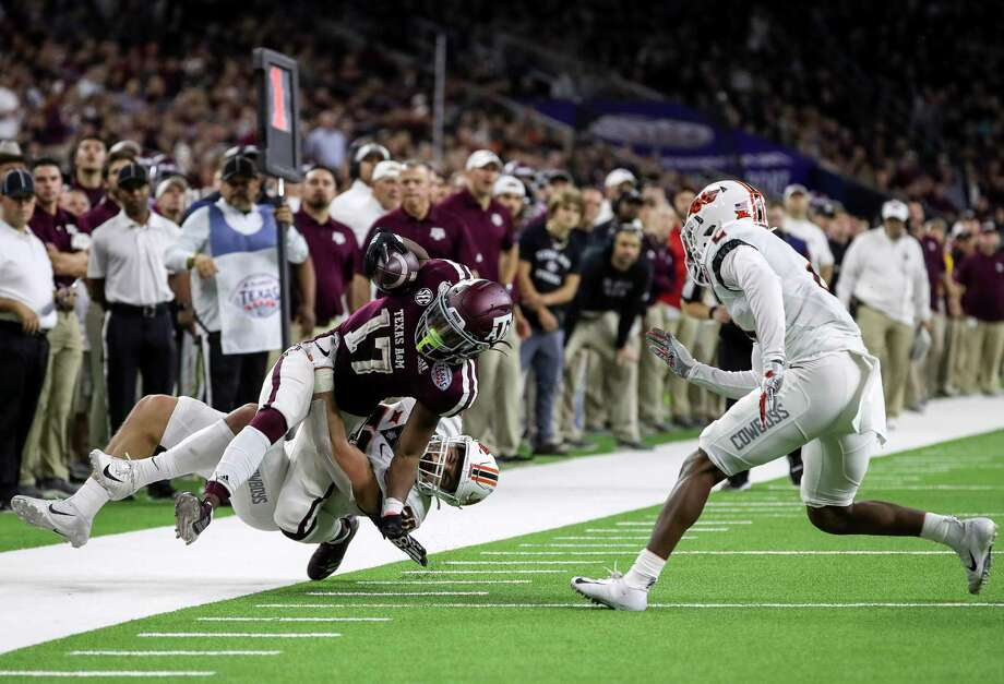 Texas A&M Aggies wide receiver Ainias Smith (17) is tackled by Oklahoma State Cowboys safety Malcolm Rodriguez (20) during the second quarter of the Texas Bowl at NRG Stadium on Friday, Dec. 27, 2019, in Houston. Photo: Jon Shapley, Houston Chronicle / Staff Photographer / © 2019 Houston Chronicle