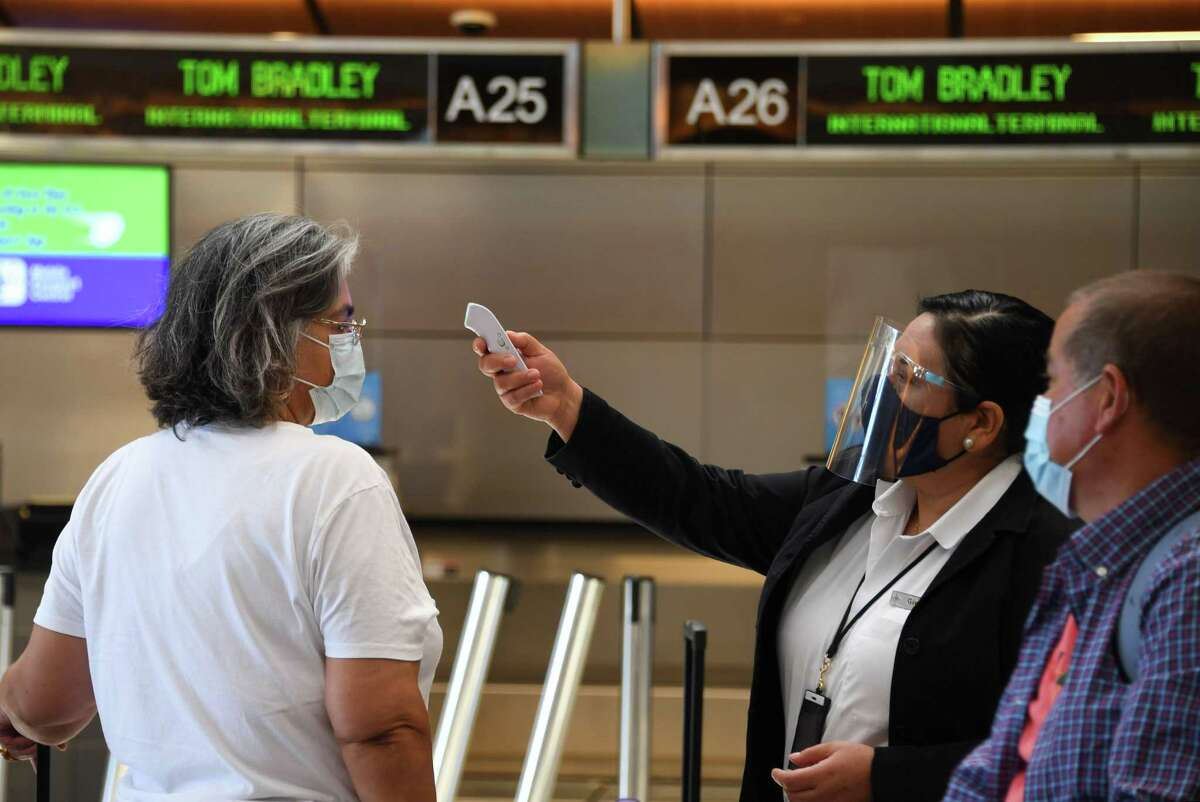 Airport employee Gigi Bebikianat checks temperatures for international travelers before allowing them to go to their gates at Los Angeles International Airport on Aug. 12, 2020. Airlines want the Transportation Security Administration, or TSA, to add temperature checks to their security clearance procedure.