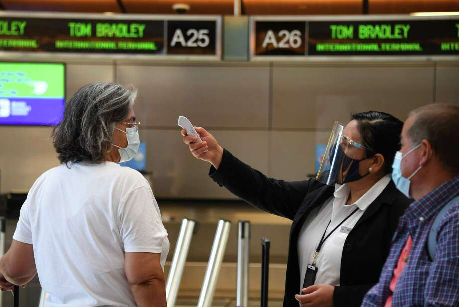 Airport employee Gigi Bebikianat checks temperatures for international travelers before allowing them to go to their gates at Los Angeles International Airport on Aug. 12, 2020. Airlines want the Transportation Security Administration, or TSA, to add temperature checks to their security clearance procedure. Photo: Robyn Beck /AFP Via Getty Images / AFP or licensors