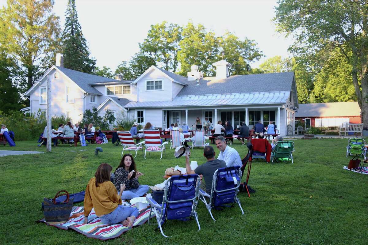 Friends enjoy the time together at the picnic dinner and music event at Wakeman Town Farm on Wednesday, Aug. 19, 2020, in Westport, Conn.