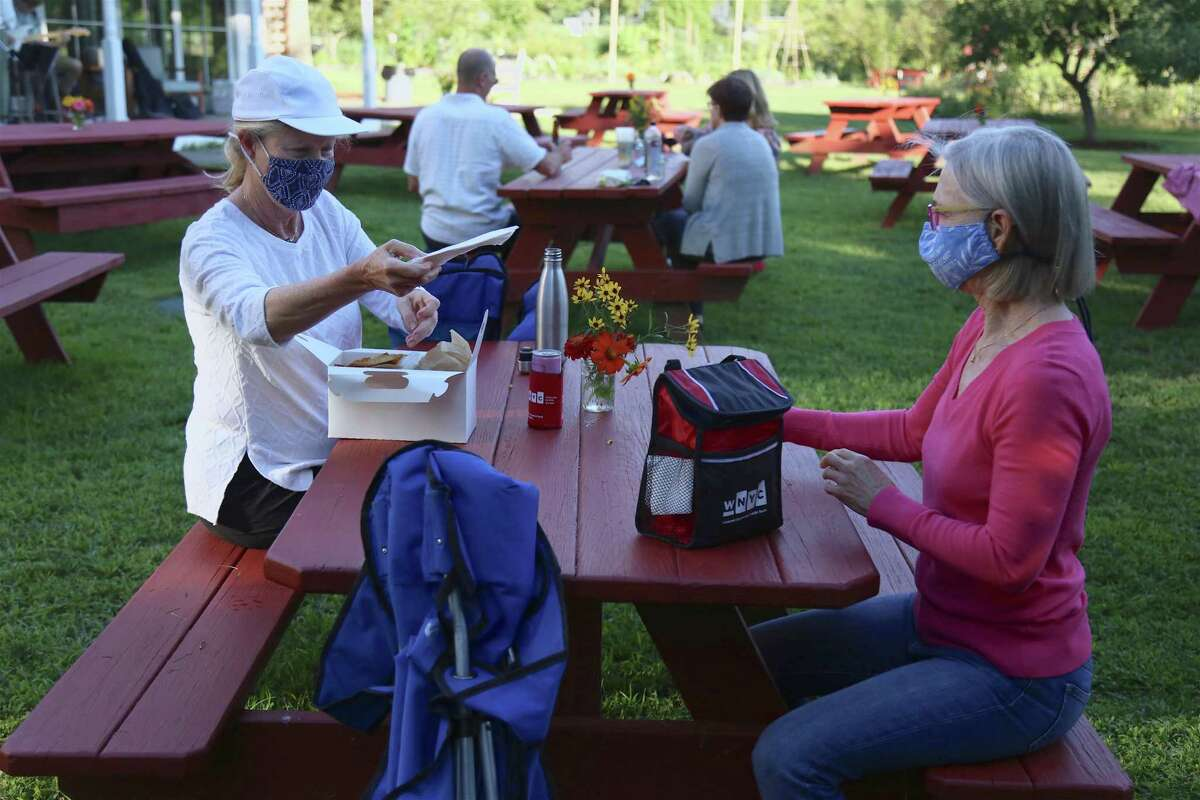 Mary Younglove, left, and Luisa Francoeur of Westport check out what's for supper at the picnic dinner and music event at Wakeman Town Farm on Wednesday, Aug. 19, 2020, in Westport, Conn.