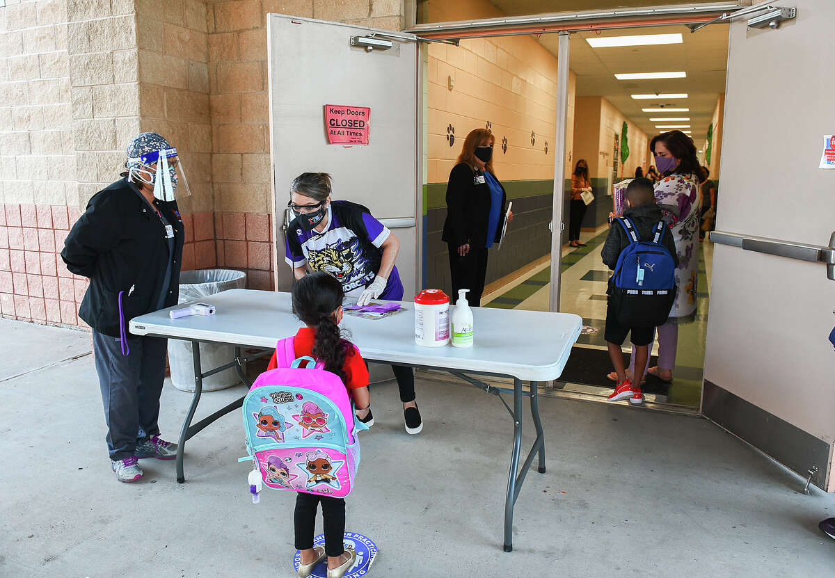 M.S. Ryan Elementary School students pass through the nurse check-in station before entering the school, Aug. 24, 2020, during the first day back to school for some students during the COVID-19 Coronavirus pandemix.