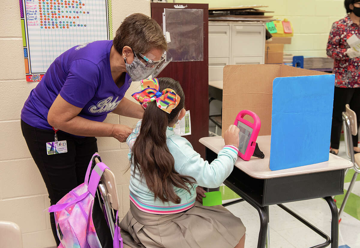 M.S. Ryan Elementary Teacher Aide Esther G. Trevino helps Lizeth Lozano log in to her virtual classroom, Aug. 24, 2020, during the first day back to school for some students during the COVID-19 Coronavirus pandemix.