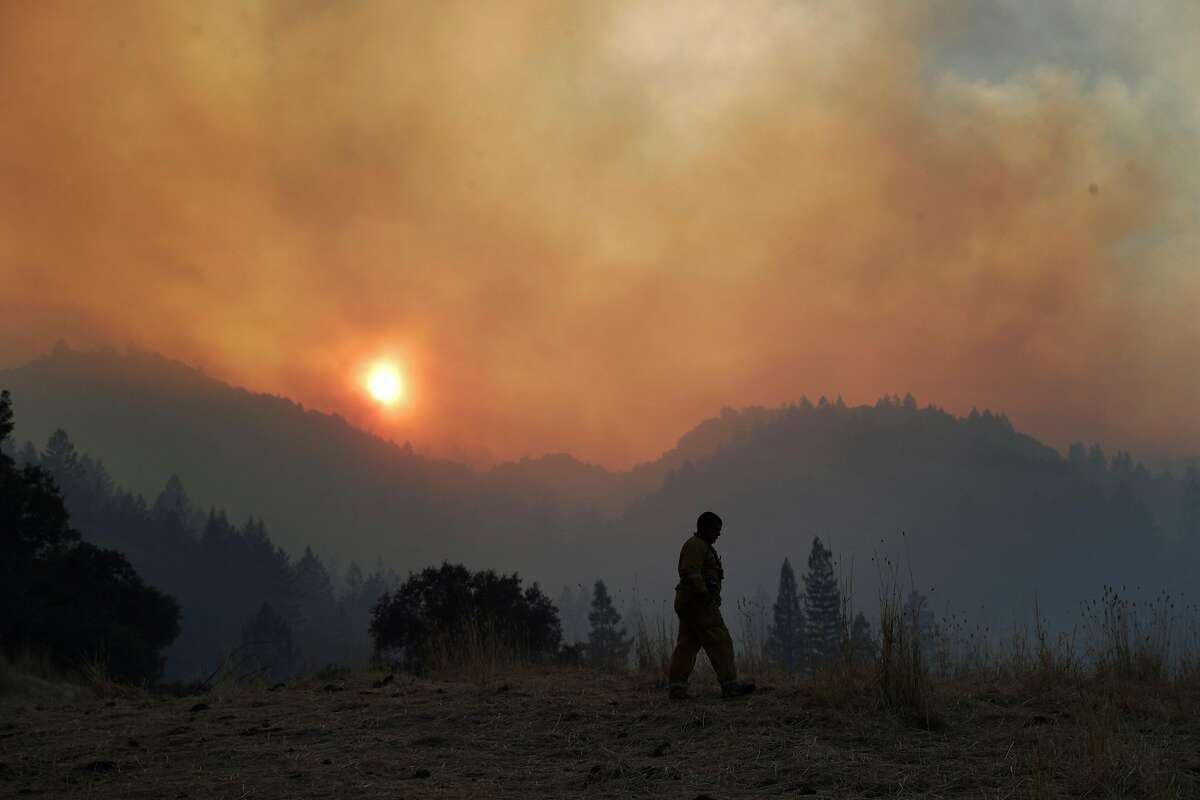 A Santa Rosa firefighter walks along a field off Wine Creek Road while conducting structure protection for the Walbridge Fire west of Healdsburg, Calif., on Friday, August 21, 2020.