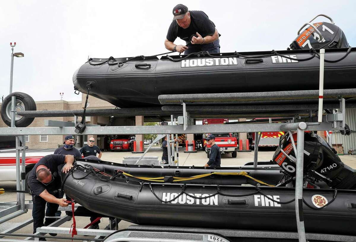 Engineer Operator Karl Carmack, left, Firefighter Paul Kessler, top, and other firefighters from Houston Fire Station 11 prepare water-rescue equipment Monday, Aug. 24, 2020, at HFD Station 11 in Houston.