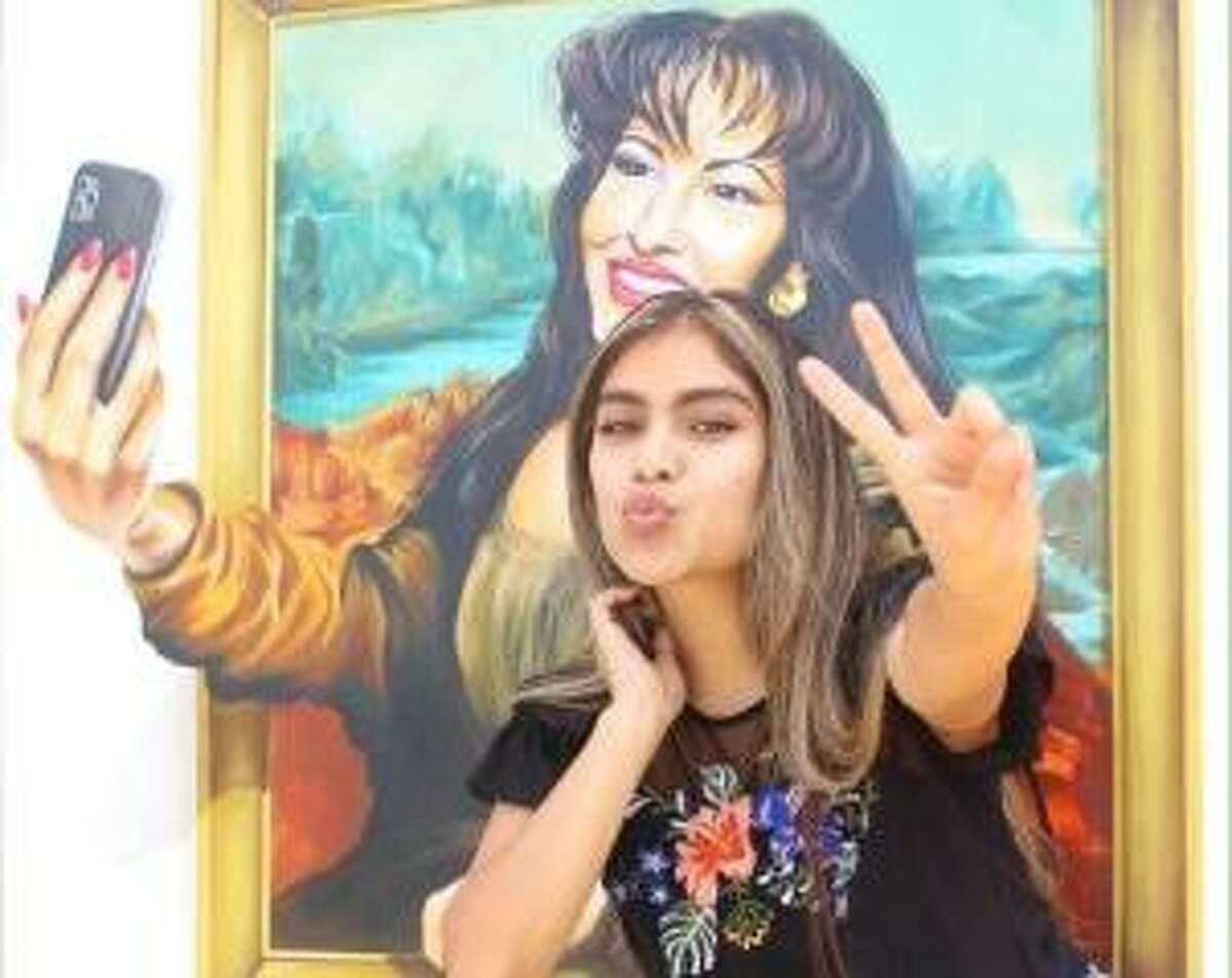 The Mona Selena painting depicting Selena Quintanilla as Mona Lisa. Using optical illusions, Mona Selena appears to extend her hand outside the painting with a cellphone to take a picture with guests.