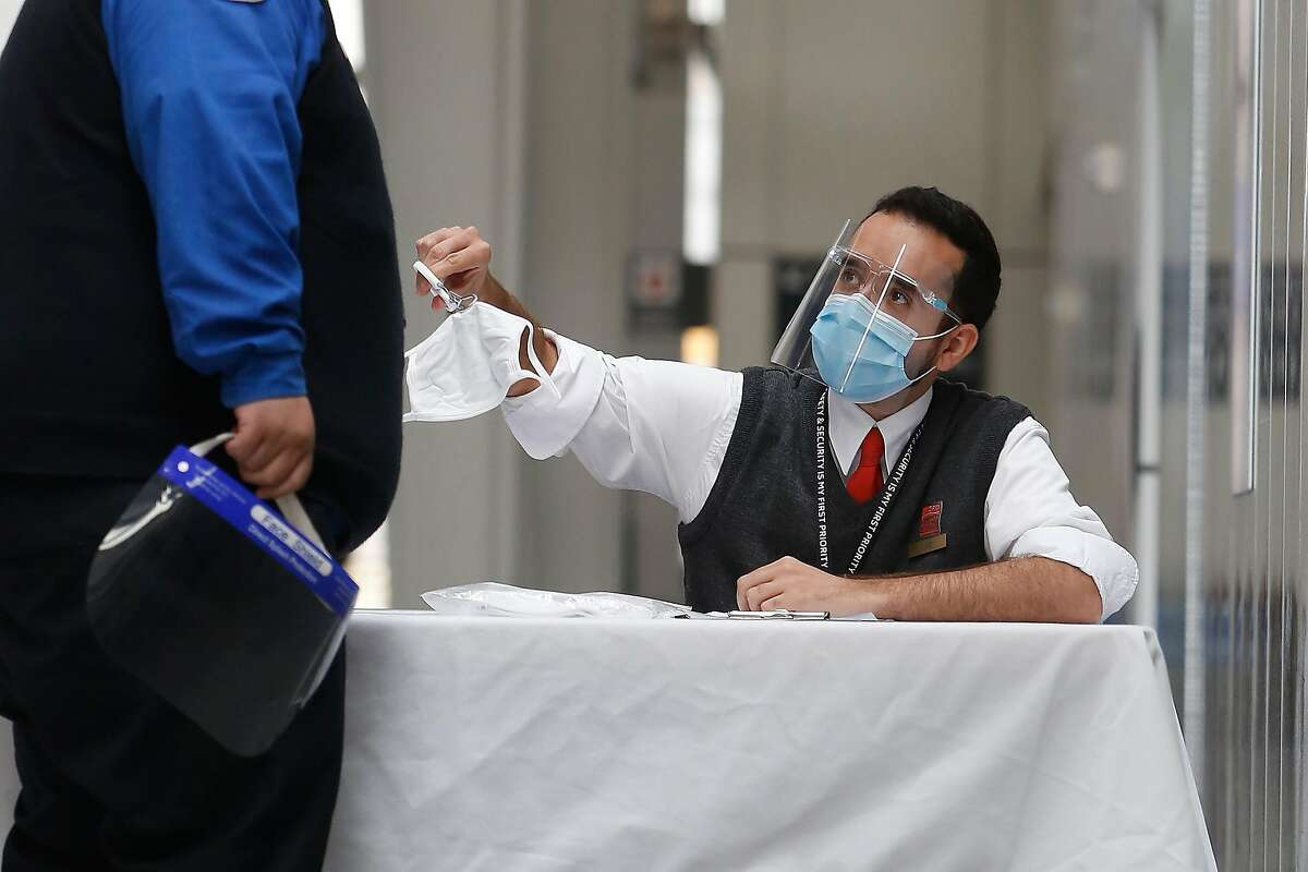 Luiz Souza, Hallmark Aviation customer care agent, uses tongs to hand out a mask as he works at a table near a security checkpoint in the International Terminal at SFO on Monday, August 24 2020 in San Francisco, Calif. Concourse A in the International Terminal at SFO has been shut since April due to the pandemic. There is a table at each terminal to hand out masks.