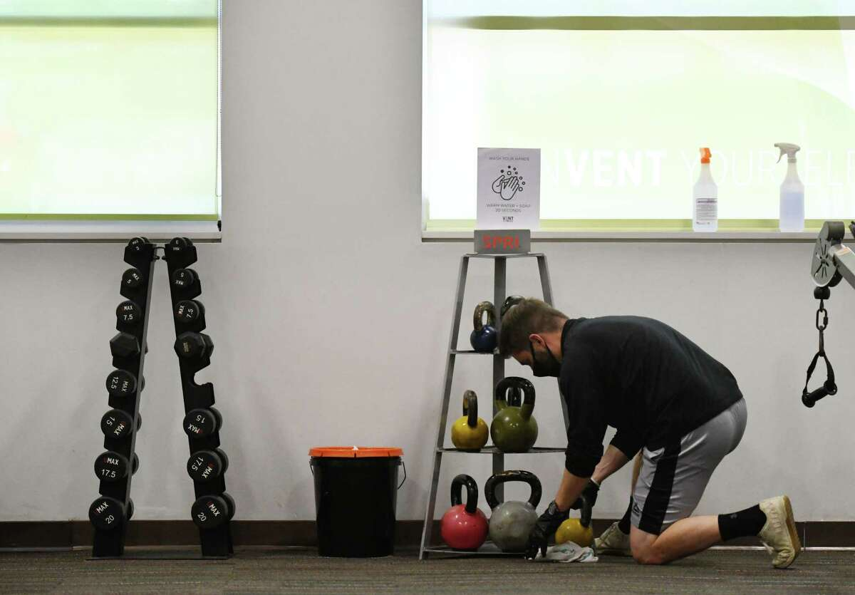 Robert McTarnaghan, a manager at Vent Fitness in Guilderland, disinfects workout equipment during the first day of gym reopening under the state's coronavirus reopening plan on Monday, Aug. 24, 2020, on Route 20 in Guilderland, N.Y. (Will Waldron/Times Union)