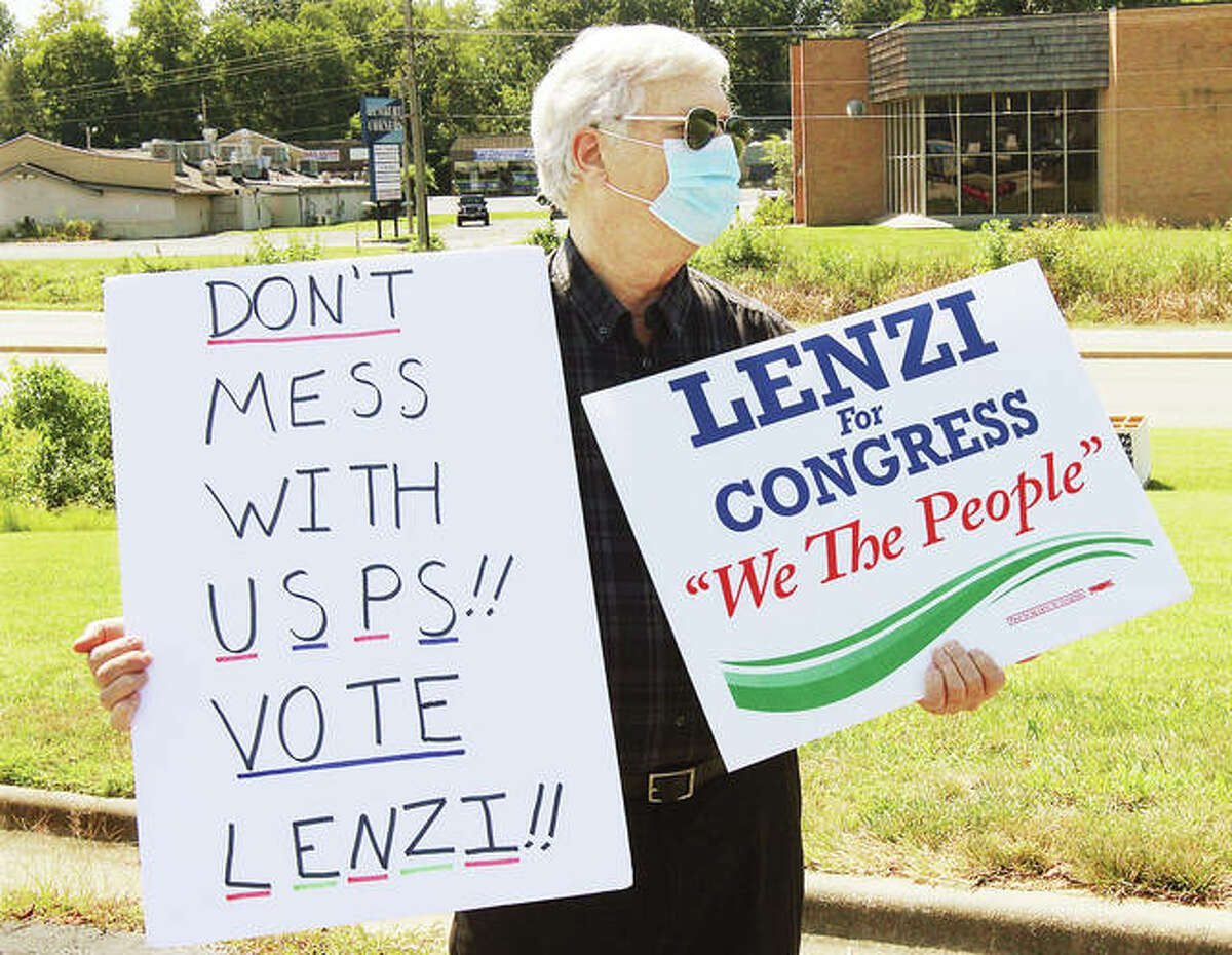 A supporter of Democratic Congressional candidate Ray Lenzi of Carbondale holds up signs Monday during Lenzi's stop at the main Alton post office. Lenzi talked to postal customers as part of a four-day tour of 17 district post offices to call for efficient and safe postal procedures for people using mail-in ballots in the upcoming election. Lenzi is challenging incumbent Rep. Mike Bost, R-Murphysboro.