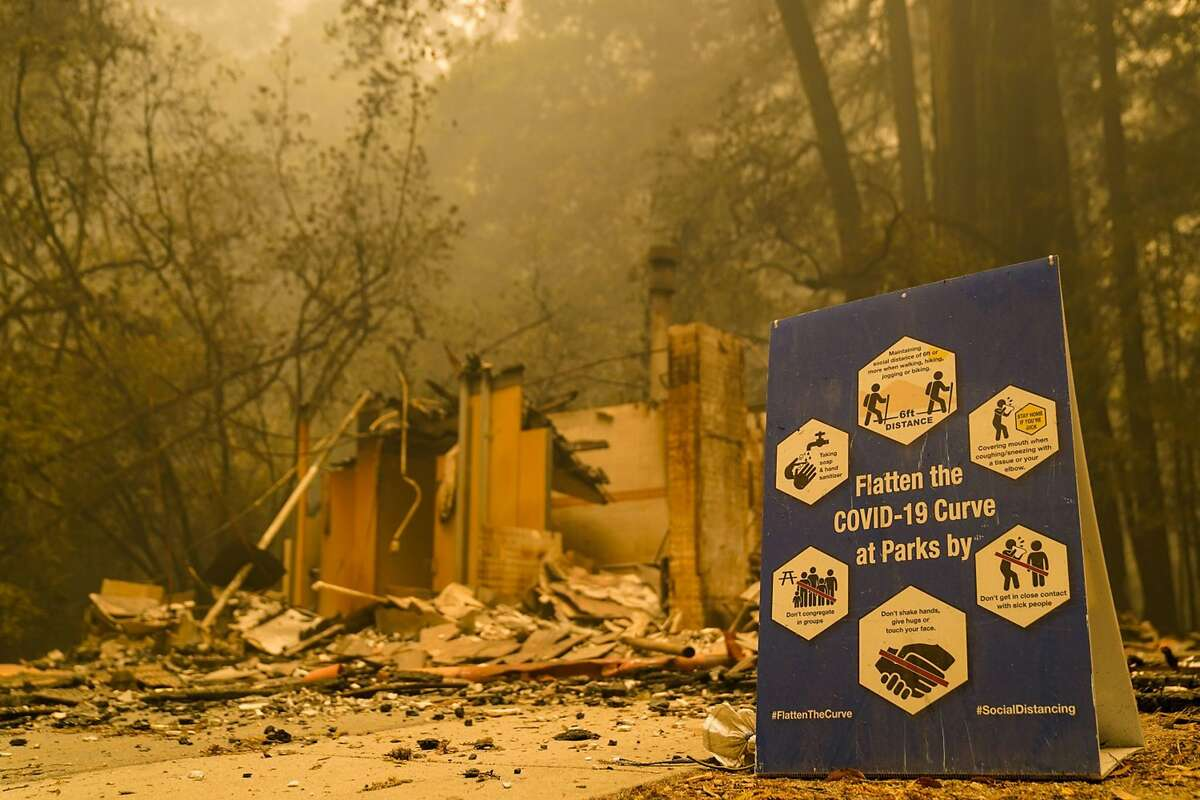 A COVID-19 sign sits in front of a burned structure while smoke hangs low in the air at Big Basin Redwoods State Park as some redwoods remain on fire on Saturday, Aug. 22, 2020 in Boulder Creek, California. The CZU August Lightning complex fires tore through Big Basin Redwoods State Park, decimating the 118-year-old state park.