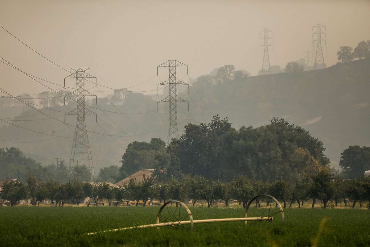 Smoke and haze surround power lines in Vacaville after the LNU Lightning Complex fire tore through the area on Monday, Aug. 24, 2020 in Vacaville, California.