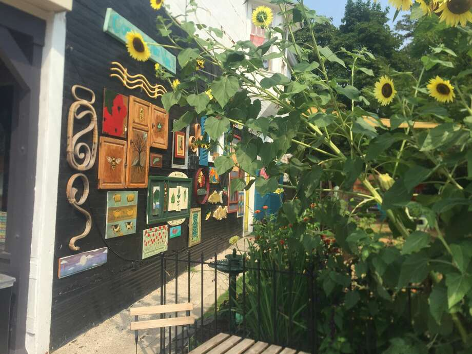 Artwork displayed at 4850 Main St. in Onekama was provided by community members to the owners of Patina and Yellow Dog Café. The art installation and landscaping was recognized by the Portage Lake Garden Club in August. Photo: Courtesy Photo