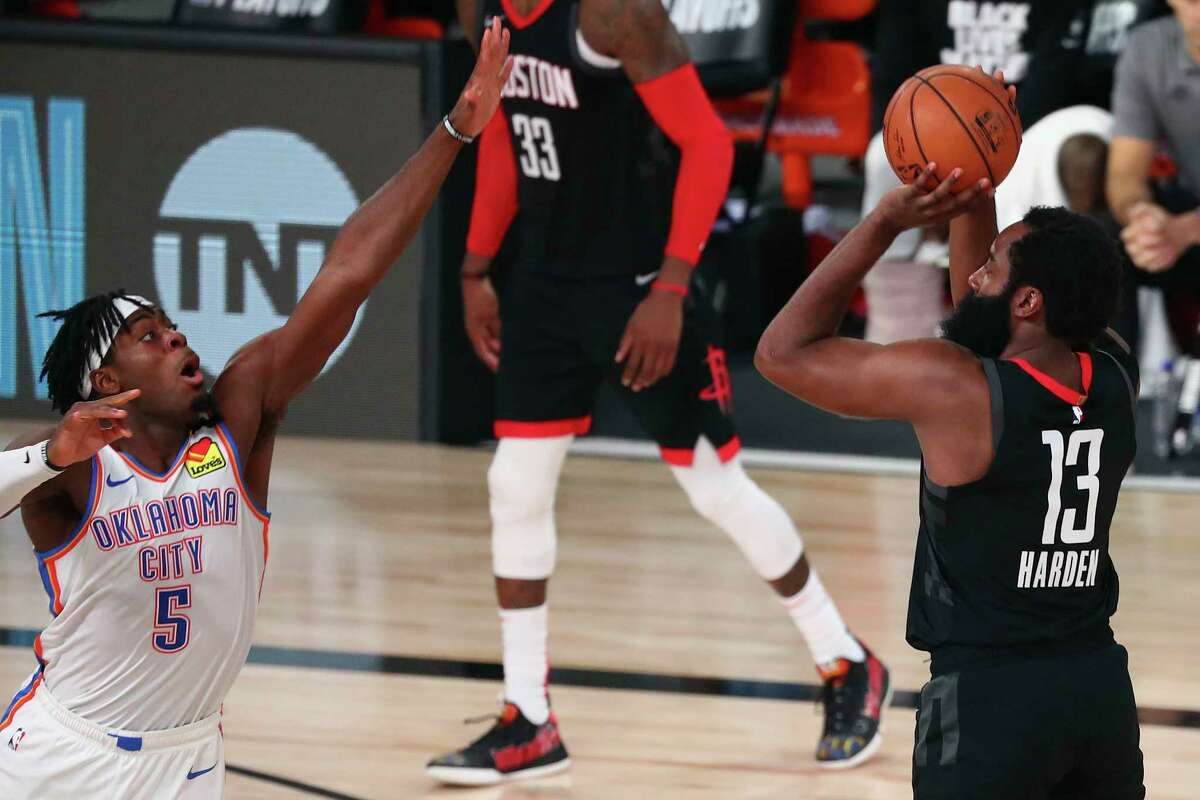 Houston Rockets guard James Harden (13) makes a three-point basket against Oklahoma City Thunder guard Luguentz Dort (5) during the second half of Game 4 of an NBA basketball first-round playoff series, Monday, Aug. 24, 2020, in Lake Buena Vista, Fla. (Kim Klement/Pool Photo via AP)