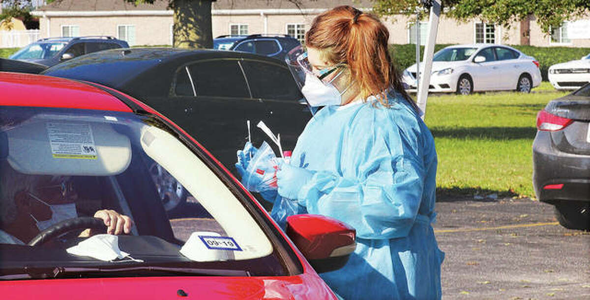 Karsyn Thompson, a medical assistant from Troy, explains the nose swabbing procedure to one of dozens of people she helped test Monday for COVID-19 at the Godfrey Village Hall on Monday. Cars were lined up dozens deep on Lars Hoffman Avenue for the testing being conducted by the Madison County Health Department.