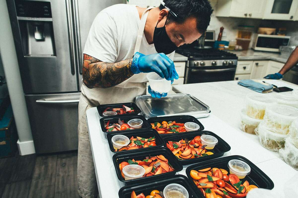 Hoang Le of Broke Ass Cooks packs side dishes for a chicken dinner in West Oakland. The pop-up was shut down by health inspectors because home kitchen operations aren't permitted in Alameda County, but that could change in the coming months.