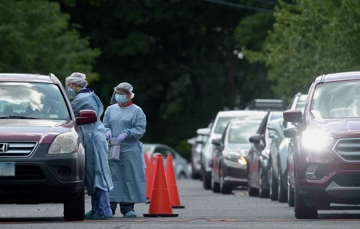Janelle Berry, left, and Aileen Morales perform a COVID-19 test at Broadview Middle School on Monday. The City of Danbury and the Community Health Center, Inc, sponsored free testing in the school's parking lot. Danbury, Conn, Monday, August 24, 2020.
