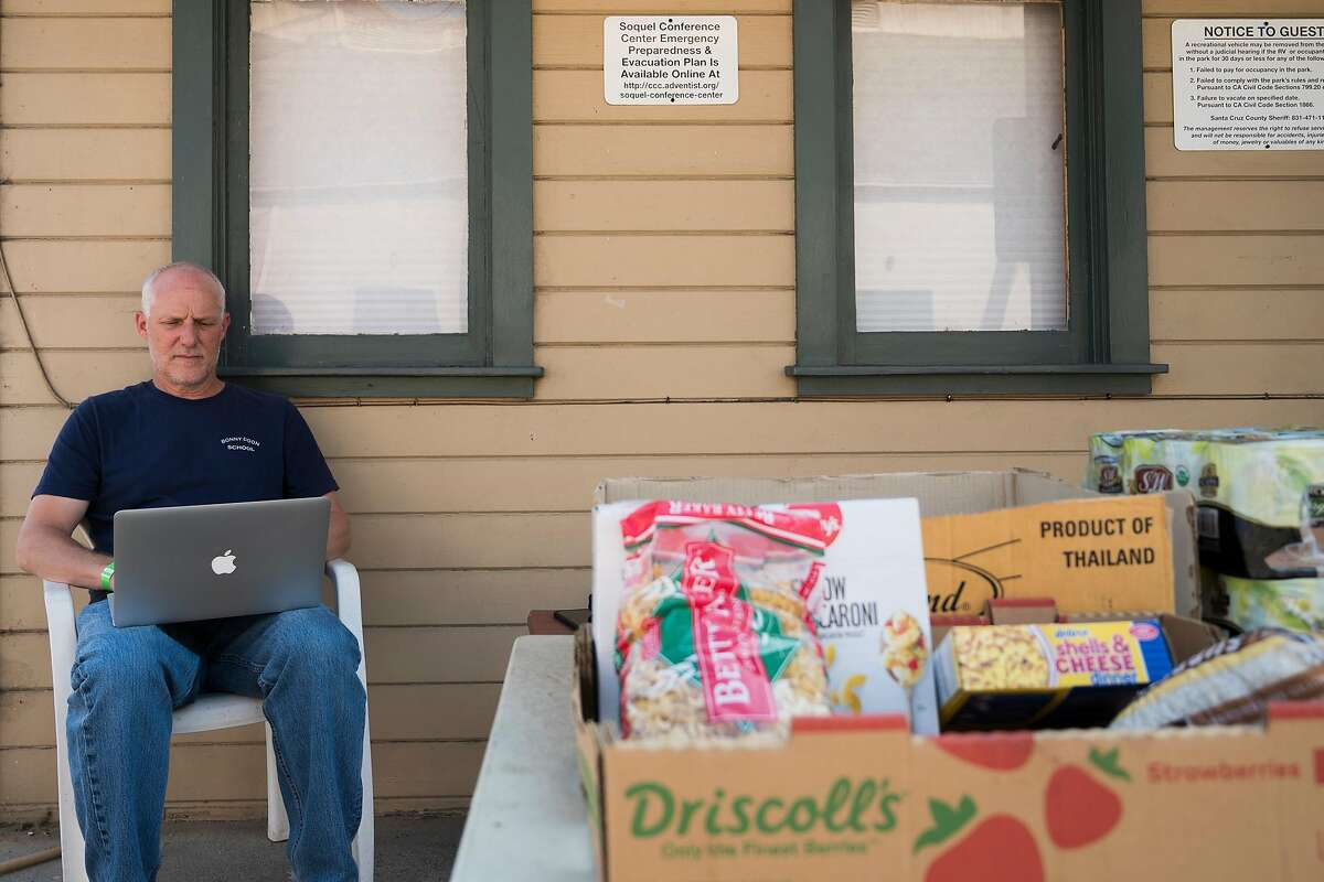Mike Heffner, Superintendent-Principal of the Bonny Doon Union Elementary School District, works on his laptop at the 7th Day Adventist church evacuation center in Soquel, Calif. on Aug., 24, 2020.