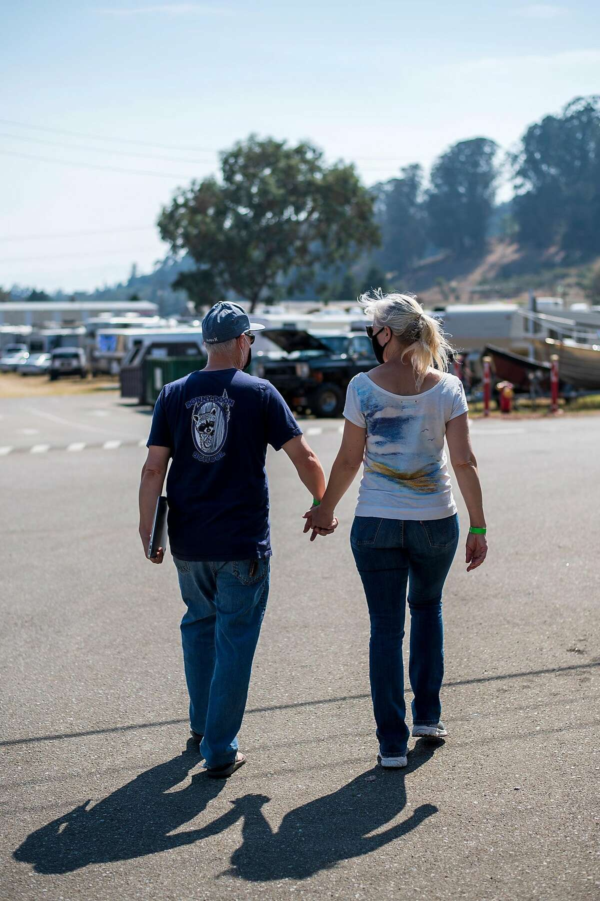 Mike Heffner, Superintendent-Principal of the Bonny Doon Union Elementary School District, (left) walks with his wife Susan through the 7th Day Adventist church evacuation center in Soquel, Calif. on Aug., 24, 2020.