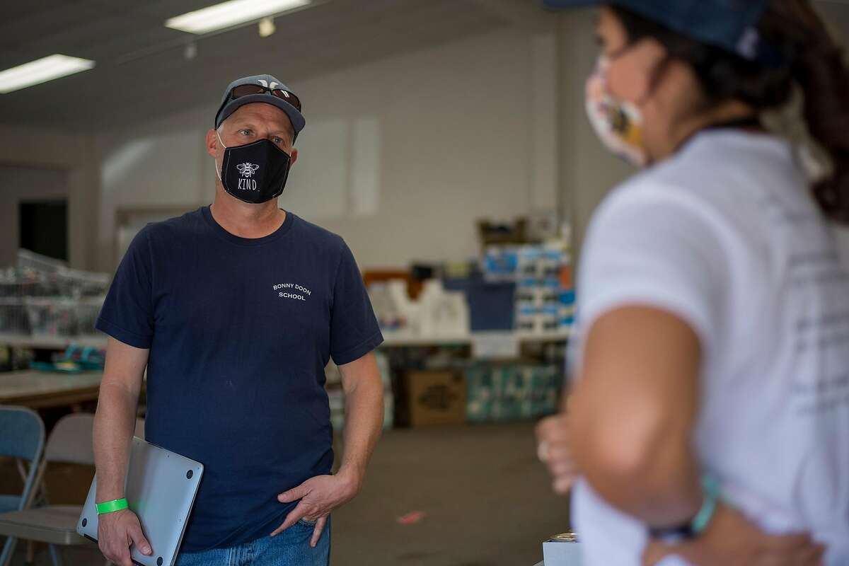 Mike Heffner, Superintendent-Principal of the Bonny Doon Union Elementary School District, (left) talks with Santa Cruz County disaster service worker Monica Hernandez at the 7th Day Adventist church evacuation center in Soquel, Calif. on Aug., 24, 2020.