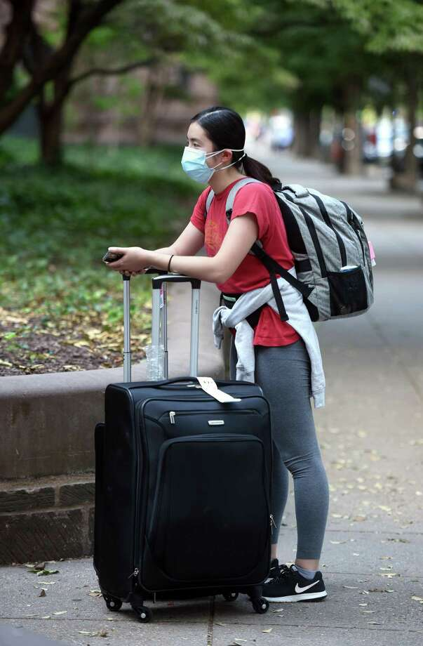 A first-year Yale University student  arriving from Iowa waits outside of the gates of Old Campus in New Haven to get into temporary overnight housing on Aug. 24, 2020. Yale University scheduled move in times up until 4:30 after which students were placed into temporary overnight housing. Photo: Arnold Gold / Hearst Connecticut Media / New Haven Register