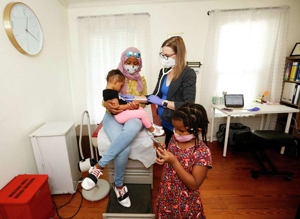 Dr. Rebecca Berens listens to the heart beat of Sereen Wheeler as she sits on her mom, Aziza Awed's, lap while her sister, Amatullah, plays a game during a check up in her Heights office in Houston on Wednesday, Aug. 12, 2020.