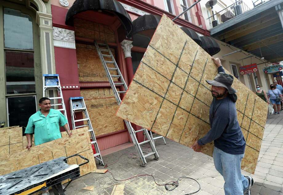 """Cesar Reyes, right, carries a sheet of plywood to cut to size as he and Robert Aparicio, left, and Manuel Sepulveda, not pictured, install window coverings at Strand Brass and Christmas on the Strand, 2115 Strand St., in Galveston on Monday, Aug. 24, 2020. Ginger Herter, who manages the shop, was erring on the side of caution boarding up the storefront as she waits to see what path Tropical Storm Laura will take as it heads toward the Texas and Louisiana coasts. """"I'd rather do this and have to take them down rather than scramble to get them up later in the week,"""" she said. ( Jennifer Reynolds/The Galveston County Daily News via AP) Photo: Jennifer Reynolds, MBR / Associated Press / © 2020 Jennifer Reynolds/The Galveston County Daily News"""