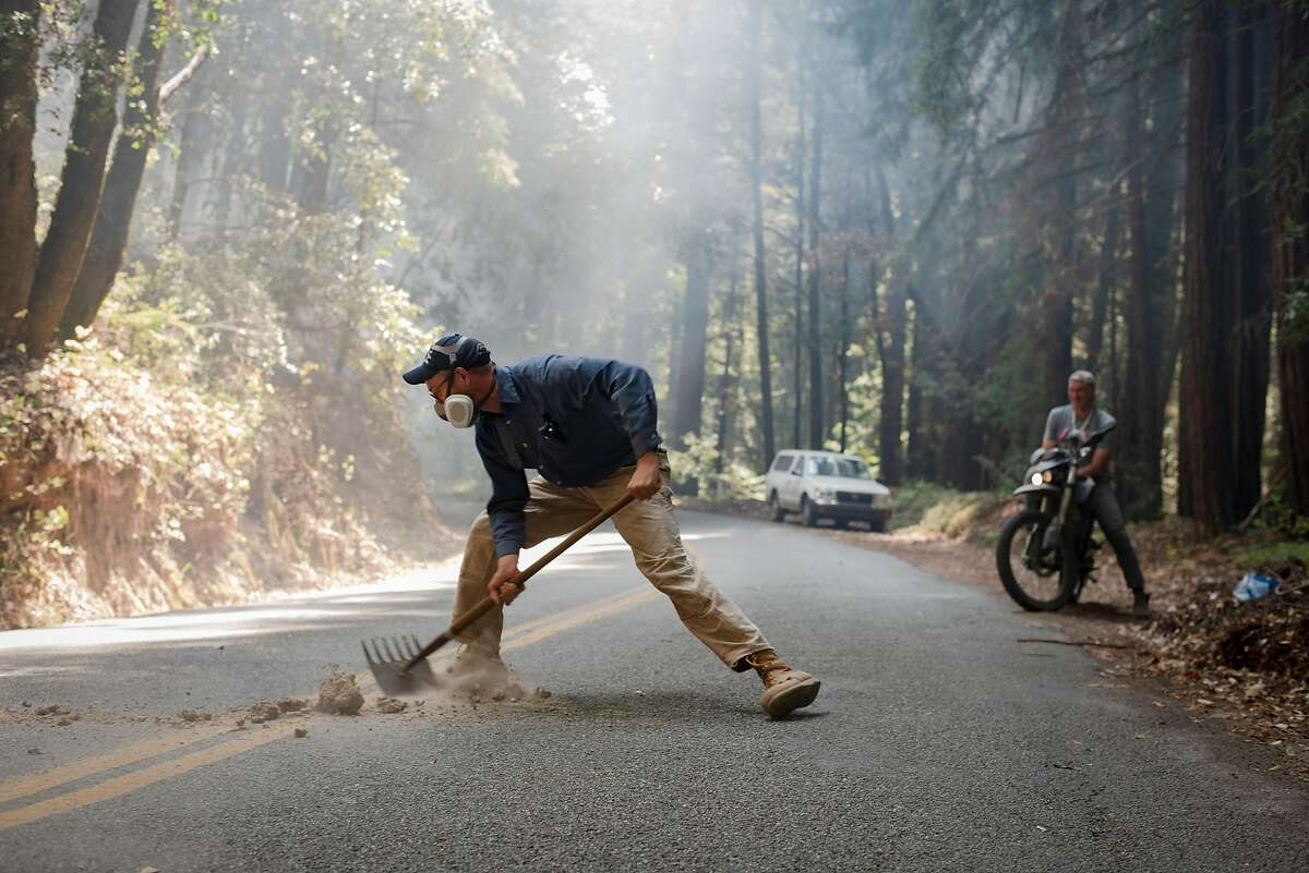 Jacob Kellner shovels fallen hot rocks back onto the other side of the Smith Grade, maintaining the fire break to defend the Boony Doon area from the CZU Lightning Complex Fire on Aug. 24, 2020. Kellner is part of a neighborhood that has banded together and stayed behind in an evacuation zone to defend their homes against the fire.