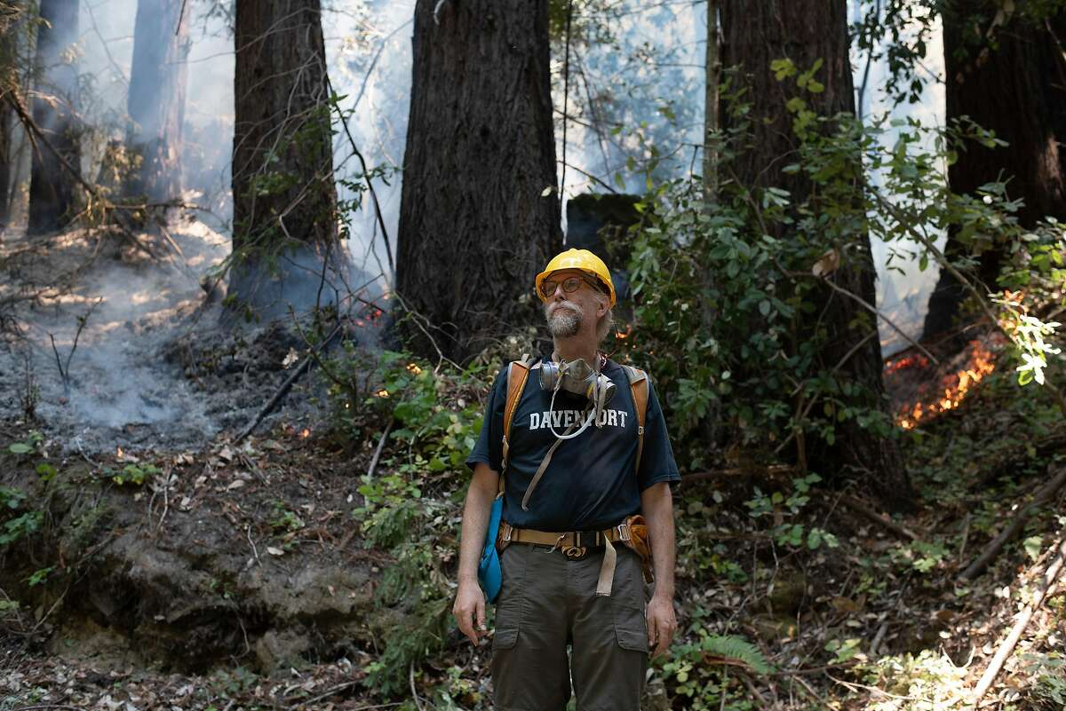 Ethan Summers stands in front of a fire break on the hillside above Smith Grade, describing his efforts to defend the Boony Doon area from the CZU Lightning Complex Fire on Aug. 24, 2020. Summers is part of a neighborhood that has banded together and stayed behind in an evacuation zone to defend their homes against the fire.