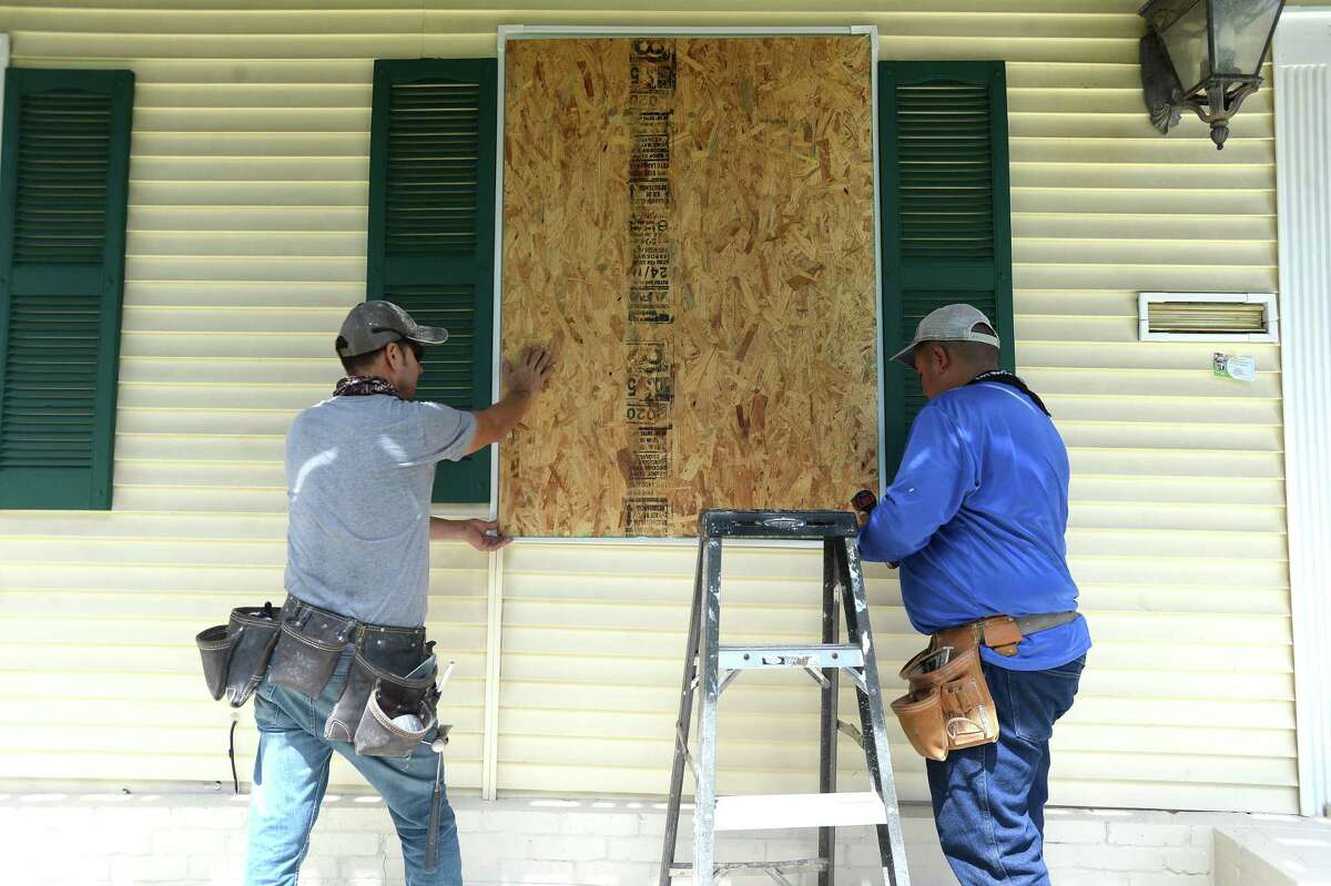 David Hernandez (left) and Pablo Garcia board up windows at the home of Francisco Ortega Monday as Ortega prepares his home in Port Arthur for Marco and Laura's hit to the region this week. Photo taken Monday, August 24, 2020 Kim Brent/The Enterprise