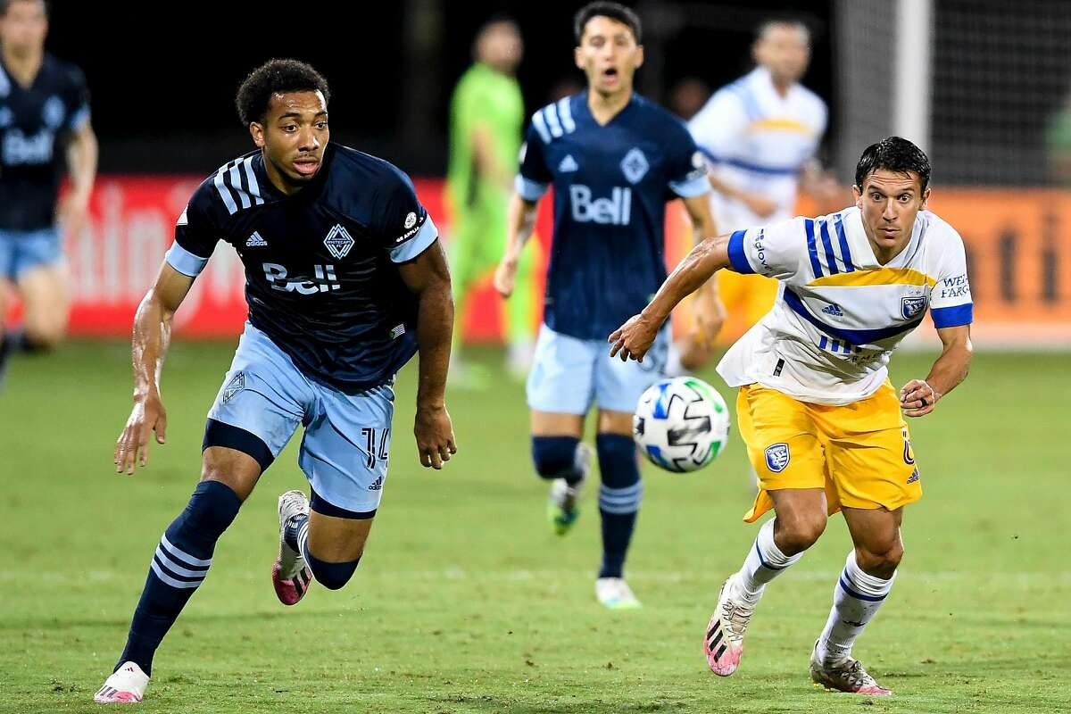 Shea Salinas #6 of San Jose Earthquakes and Theo Bair #14 of Vancouver Whitecaps charge the ball during the second half in the MLS is Back Tournament at ESPN Wide World of Sports Complex on July 15, 2020 in Reunion, Florida.