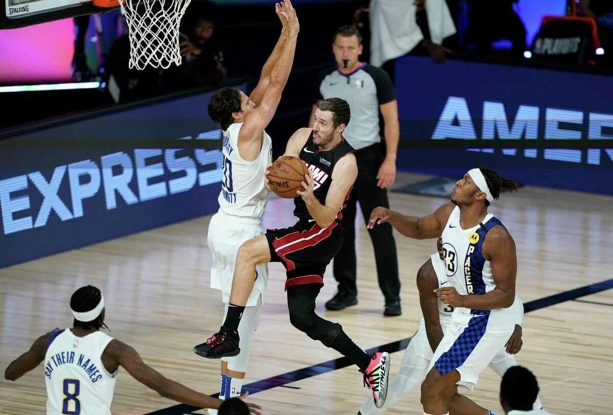 Miami Heat's Goran Dragic (7) shoots around Indiana Pacers' Doug McDermott (20) during the second half of an NBA basketball first round playoff game Monday, Aug. 24, 2020, in Lake Buena Vista, Fla. (AP Photo/Ashley Landis, Pool)