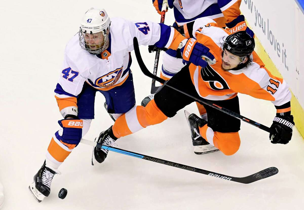 New York Islanders right wing Leo Komarov (47) pushes Philadelphia Flyers right wing Travis Konecny (11) off the puck behind the net during second-period NHL Stanley Cup Eastern Conference playoff hockey game action in Toronto, Monday, Aug. 24, 2020. (Frank Gunn/The Canadian Press via AP)