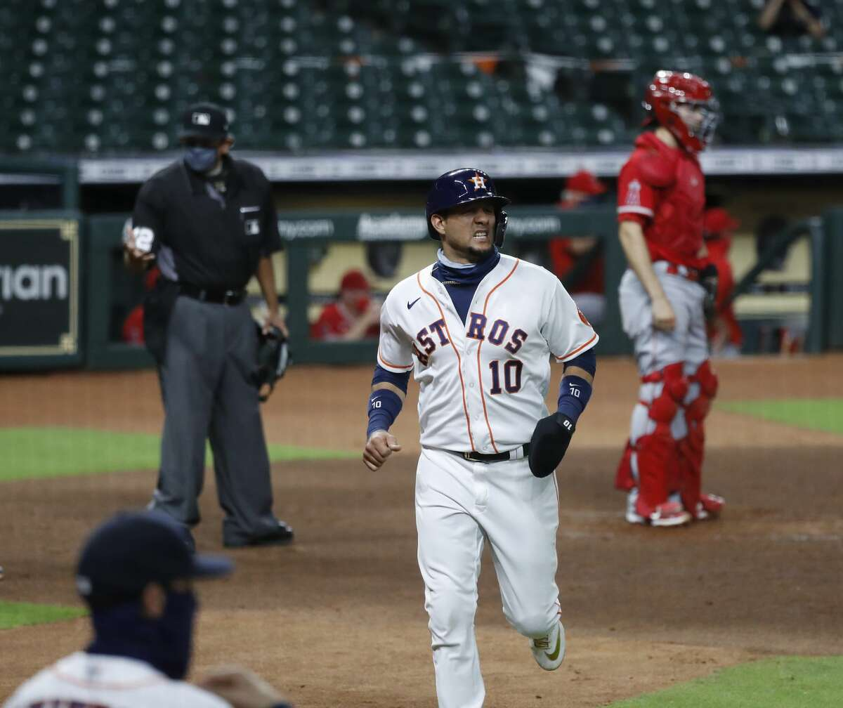 Houston Astros Yuli Gurriel (10) scores a run on Houston Astros Michael Brantley's RBI double during the third inning of an MLB baseball game at Minute Maid Park, Monday, August 24, 2020, in Houston.