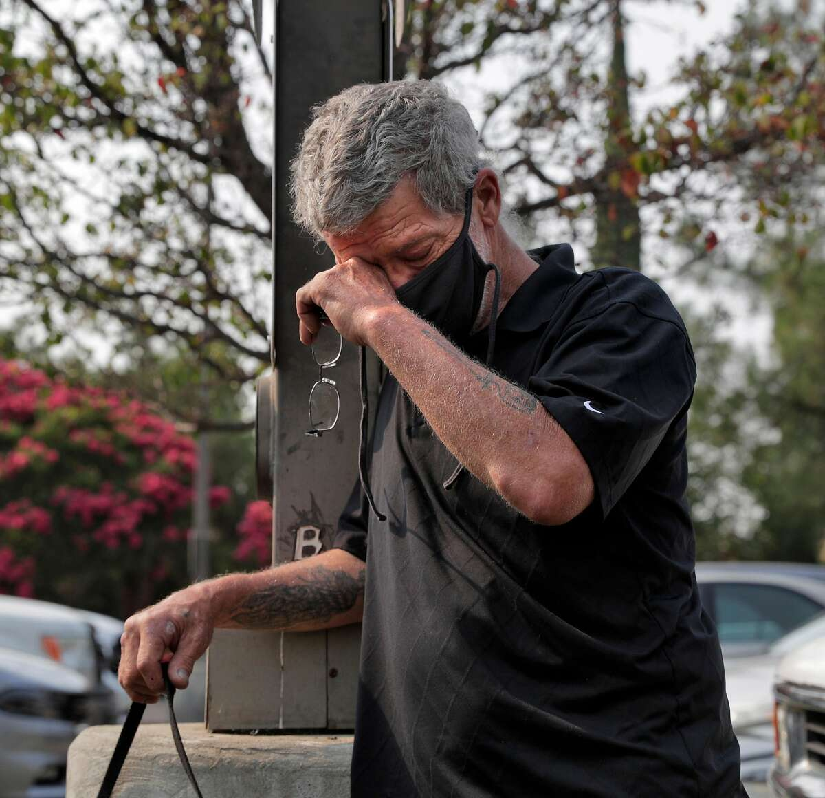 David Mackert wipes his eyes as he recollects the devastation to his friend's ranch in the parking lot at the Extended Stay America where he evacuated as the local fires continued to keep people from returning to their home in Fairfield, Calif., on Monday, August 24, 2020.