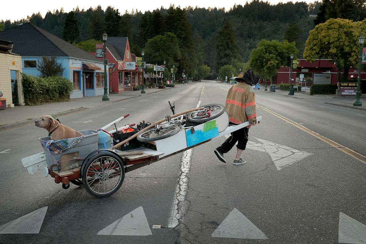 Eric Rathe, of Guernville, moves his belongings to a safer location on a makeshift rickshaw with his dog Frisco on the back as the local fires continued to keep people from returning to their home in Healdsburg, Calif., on Monday, August 24, 2020.