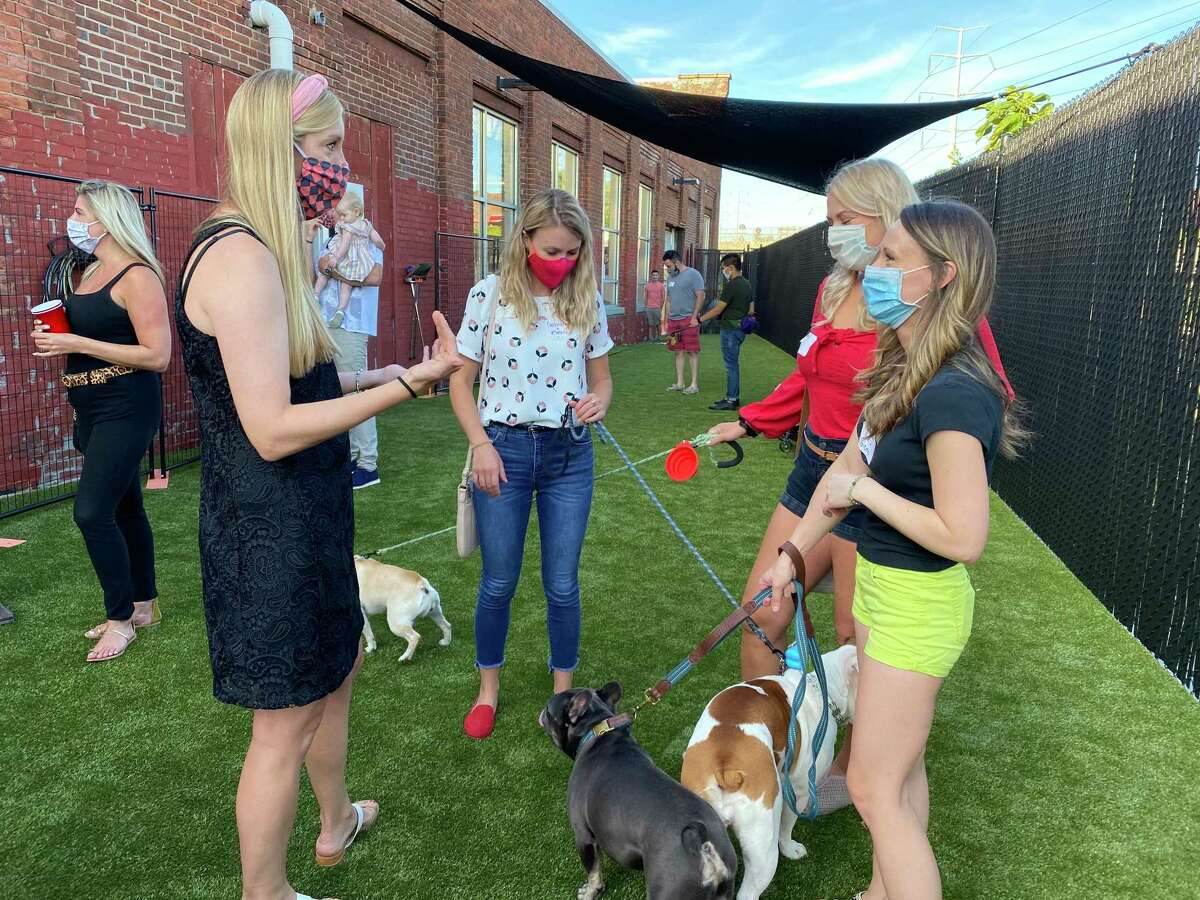 Jackie McFayden, co-owner of Paw Haven, with friends and visiting pets at Paw Haven.