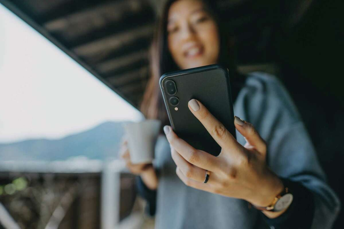 Young Asian woman using smartphone while relaxing with coffee in the balcony on a fresh morning