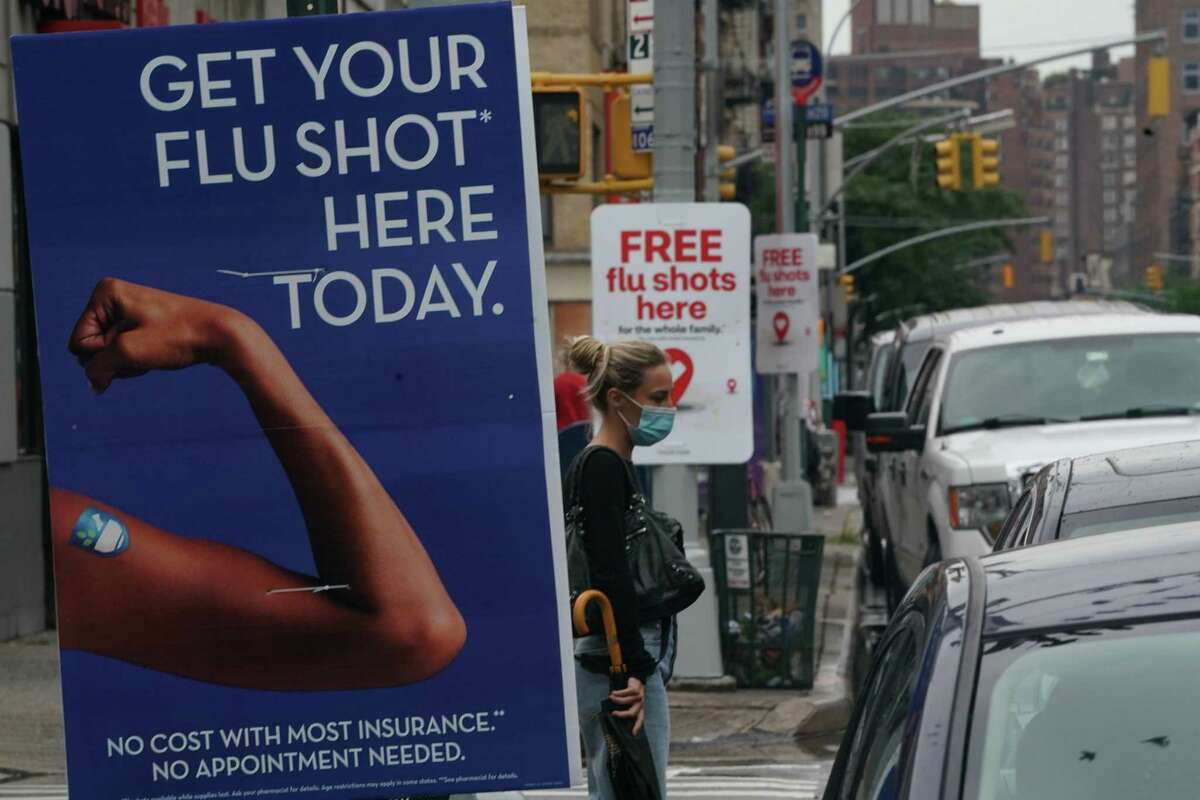 A woman walks past free flu shot advertisements outside of drugstores on August 19, 2020 in New York. Health officials say flu shots are especially important this year to avoid a