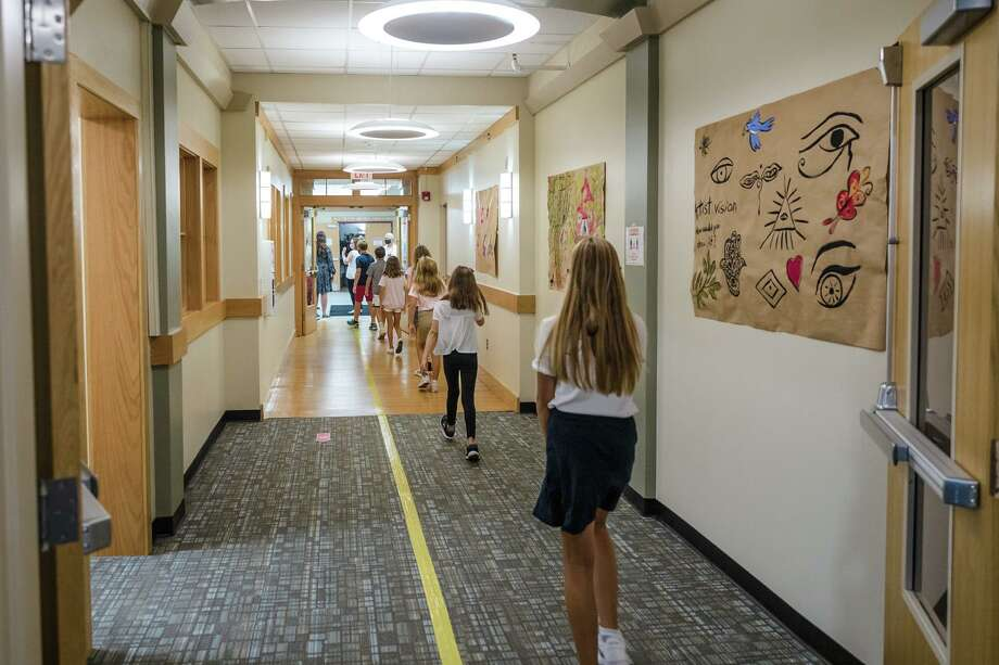 Fifth graders at St. Luke's School in New Canaan get accustomed to hallways marked to keep students apart to minimize the risk of spreading COVID-19. A teacher at the school has tested positive for the virus, the school announced Monday. Photo: Contributed Photo / @ St. Luke's School