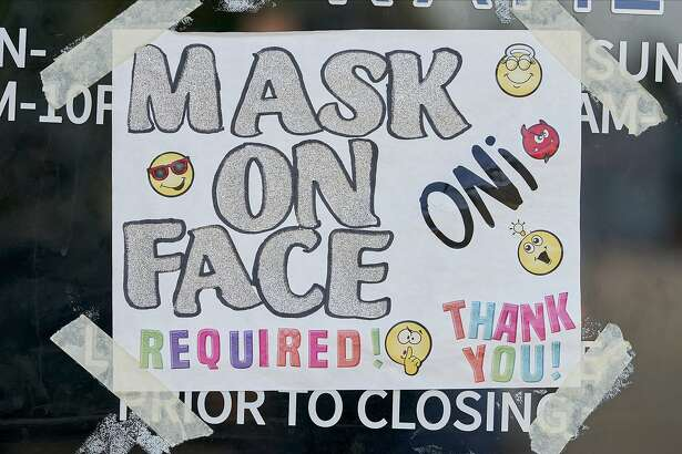 A sign requiring visitors to wear masks at a restaurant in Dallas, Texas, U.S., on Monday, Aug. 17, 2020. Texas officials have launched an investigation into why statewide Covid-19 data showed a record surge in positive-test rates even as hospital admissions and other metrics indicate the virus's spread is slowing. Photographer: Cooper Neill/Bloomberg