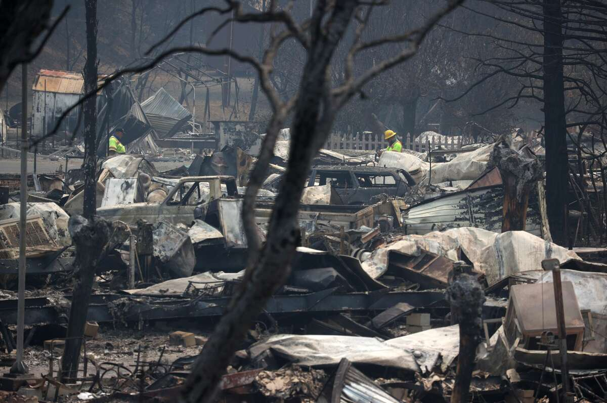 Utility workers survey the damage a mobile home park that was destroyed by the LNU Lightning Complex fire on August 24, 2020 in Napa, California.