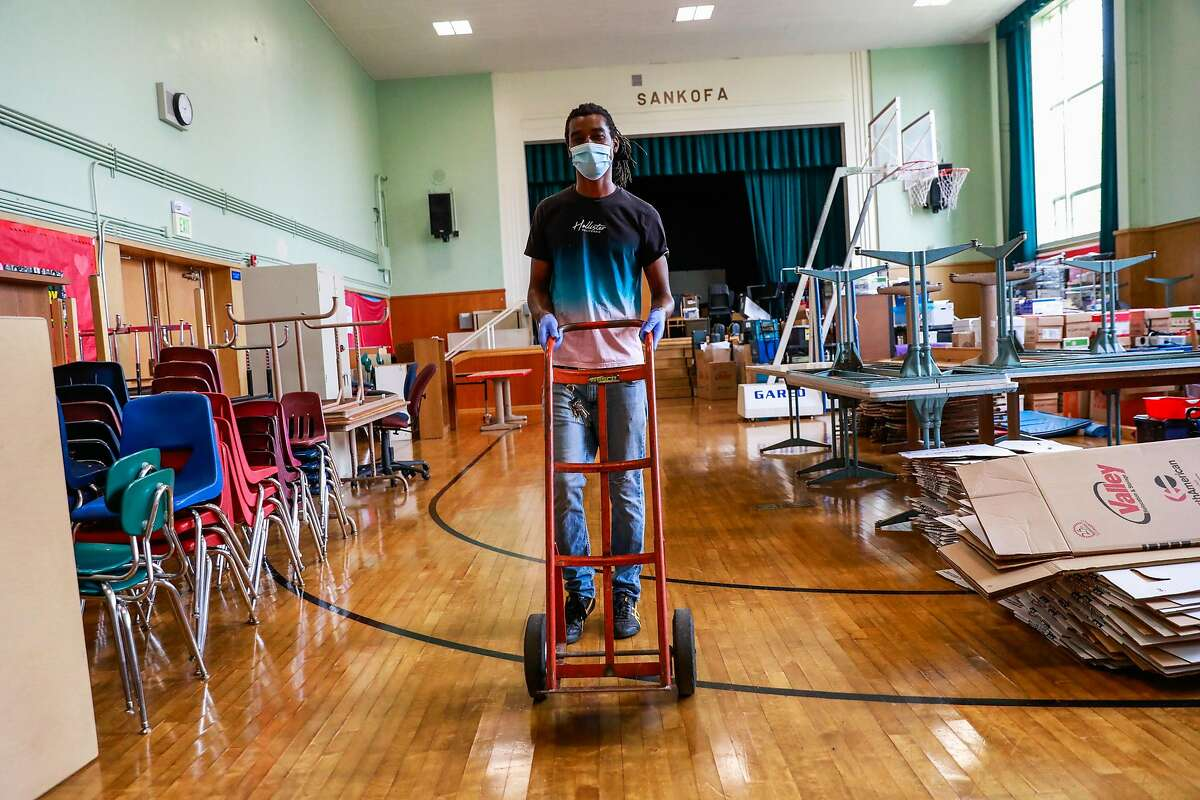 Head custodian Ashanti Lewis pushes a dolly as he works on organizing the assembly room at Sankofa Academy on the first day of school on Monday, Aug. 10, 2020 in Oakland, California.