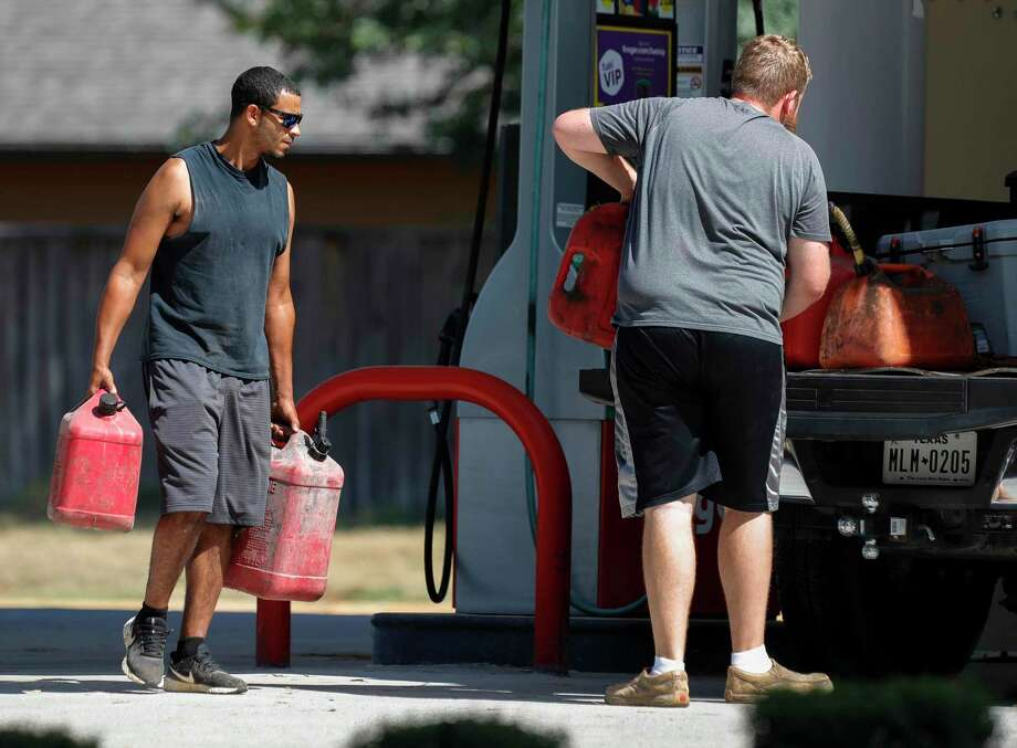 Jacob Lewis, left, helps Colby Woody carry filled-up fuel containers to the back of his truck at a gas station off South Loop 336 in preparation for Hurricane Laura, Tuesday, Aug. 25, 2020, in Conroe. Photo: Jason Fochtman, Houston Chronicle / Staff Photographer / 2020 © Houston Chronicle