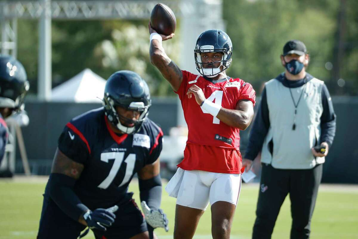 Houston Texans quarterback Deshaun Watson (4) throws a pass over offensive tackle Tytus Howard (71) during an NFL training camp football practice Tuesday, Aug. 25, 2020, in Houston.