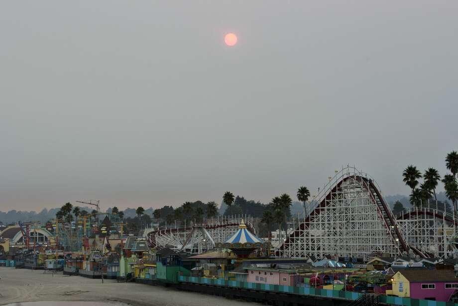 The sun is seen through the smoke of the CZU Lightning Complex Fire as it sets behind the Santa Cruz Beach Boardwalk in Santa Cruz, Calif., on Friday, Aug. 21, 2020. Photo: MediaNews Group/The Mercury News Via Getty Images/MediaNews Group Via Getty Images / Bay Area News Group