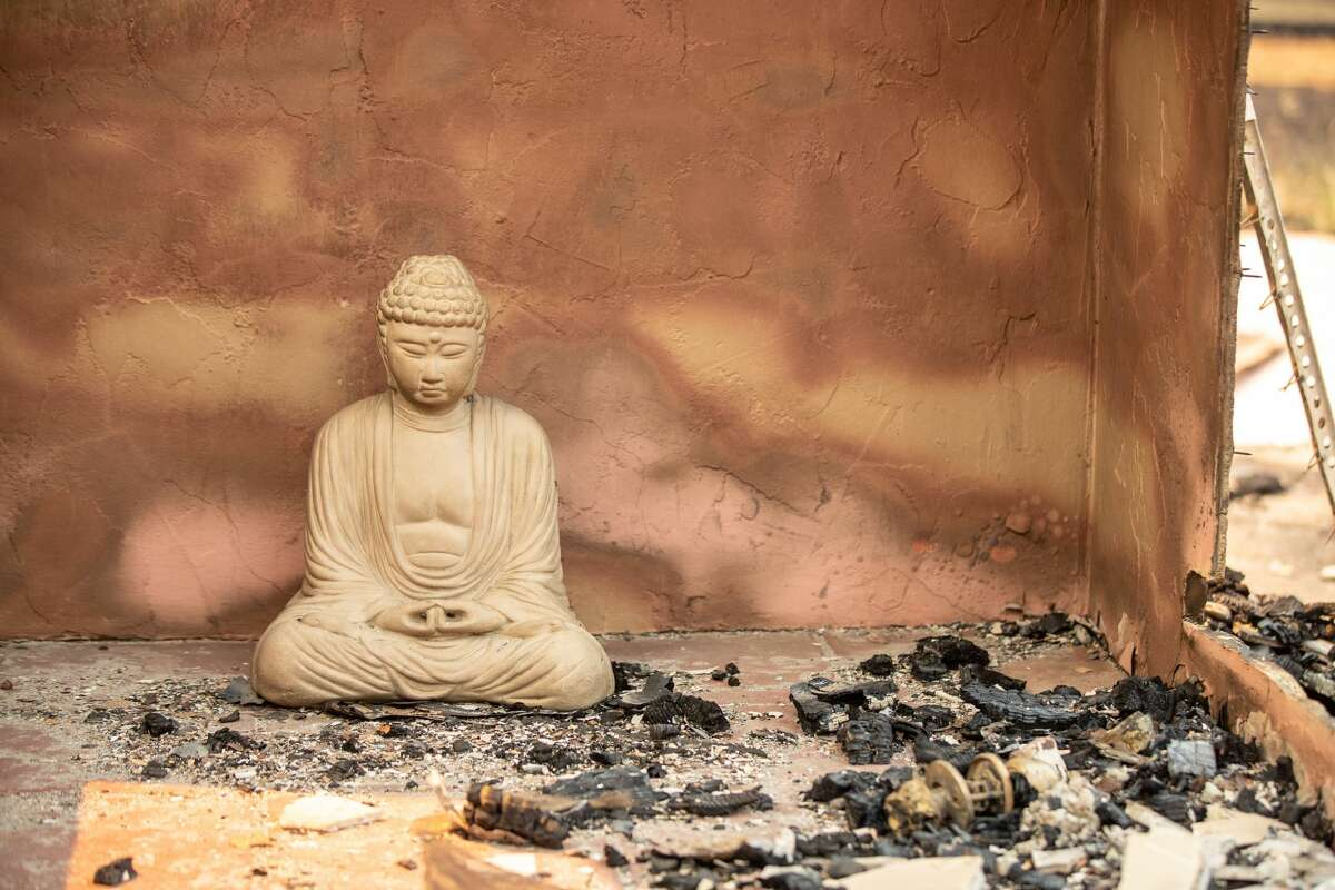 A Buddha statue sits among the remains of a house destroyed by the LNU Lightning Complex fire on Wallace Creek Road in Healdsburg, Calif., on Friday, Aug., 21, 2020.
